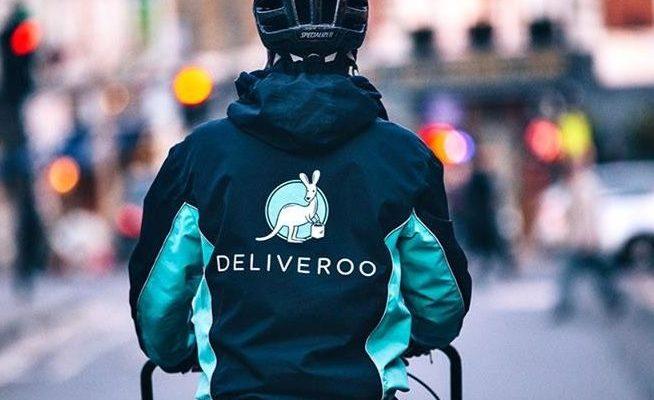 Un livreur de Deliveroo de dos sur sa bicyclette