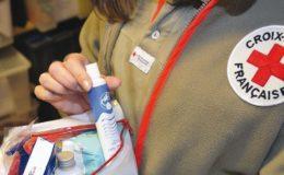 Une bénévole de La Croix Rouge tenant un panier de produits de première necessité.